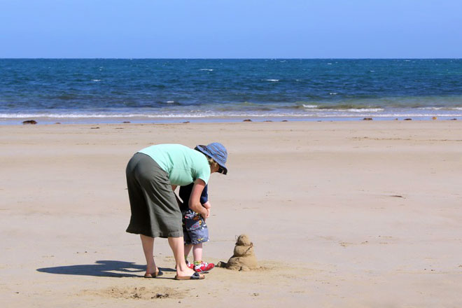 Lady and her son saying hello to George the sand snowman.