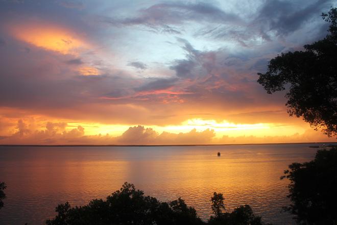 Bright yellow-orange sky among a receding pink-blue horizon.