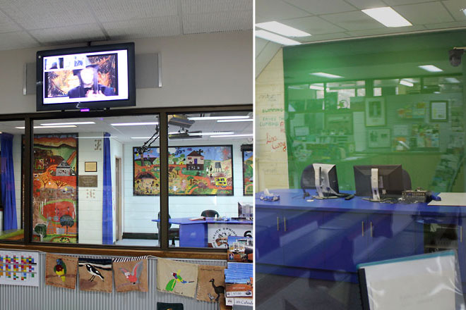 Behind glass windows is the teacher's classroom, with a green screen.