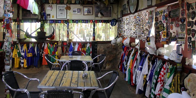 Seating by the bar. Helmets and jerseys along the wall.