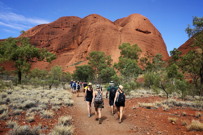 Tour mates walking towards Kata Tjuta rock formations in the background.