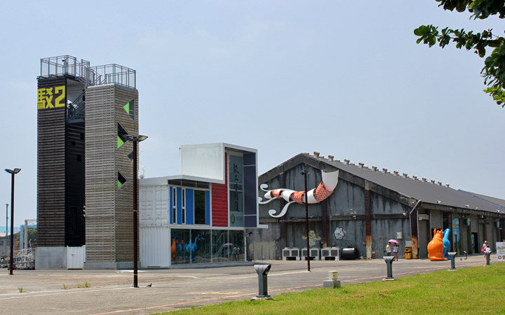 2 watch towers, a very boxy building and a warehouse with a flying kite sculpture on its front.