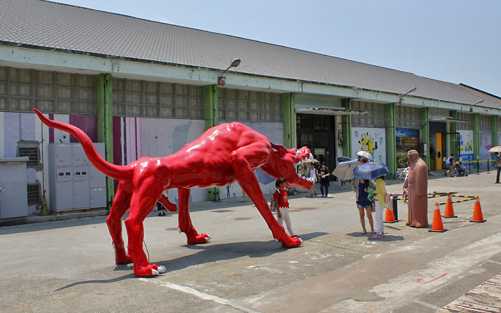 Life-size red monster and man statue.