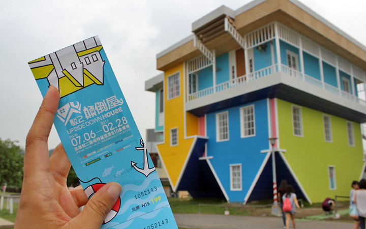 Upside down house in background, ticket in the foreground.