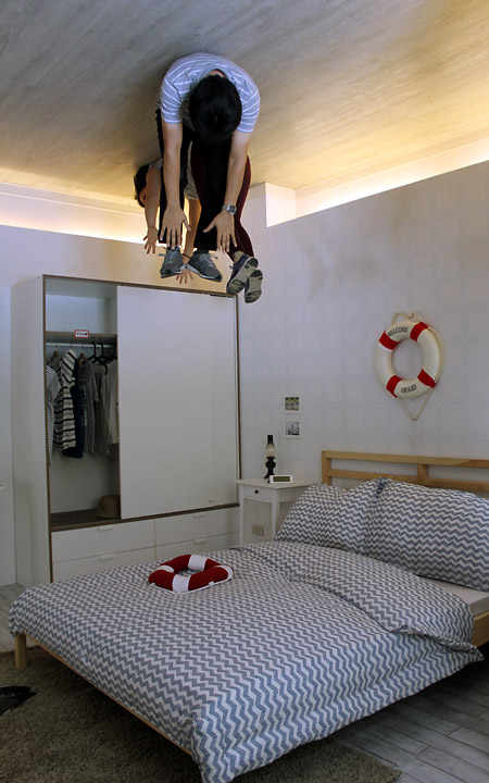 2 people on the ceiling. Reaching out for the bed.